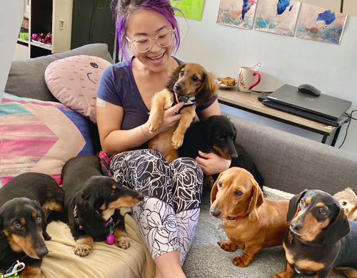 Image is of an Asian woman sitting on a couch. She is surrounded by a number of little dogs. She holds one in her lap and is smiling. Inform National Pain Week.
