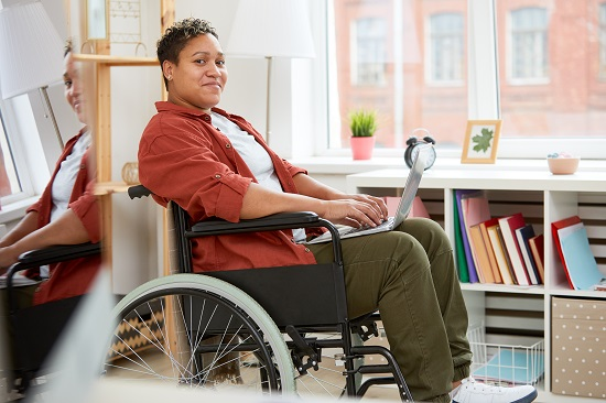 Image is of a black woman using a wheelchair. She sits side on to the camera and has a laptop open on her knees. She wears brown pants, a grey tshirt and a red shirt, open and with the sleeves rolled up to her arms. She is working from home.