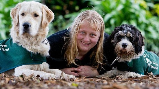 Image is of a white woman (Katie Hunter, the founder of Dogs for Kids) crouched between two dogs, one a medium sized yellow Labrador and one a small terrier.