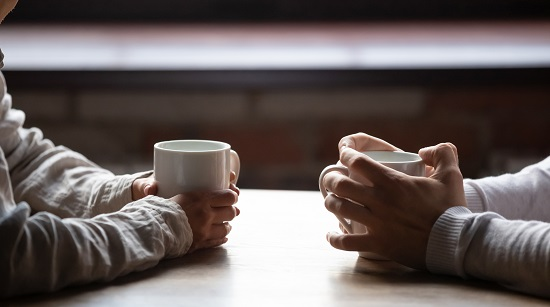 Image is a close up of two people sitting in a cafe, holding warm cups of coffee on table. Inform new relationship blog.