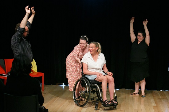 Four actors perform in front of a black curtain at Meeting Place 2019. One woman, wearing an orange and white floral dress, pushes another woman, wearing a denim skirt and a white shirt, in her manual wheelchair. The woman pushing the wheelchair is leaning quite low as her arms are unusually short. Both women are smiling. A man in a black and white stripped shirt stands to their right, a woman in a black shirt stands to their left. Both face the women between them with their arms held high in the air.