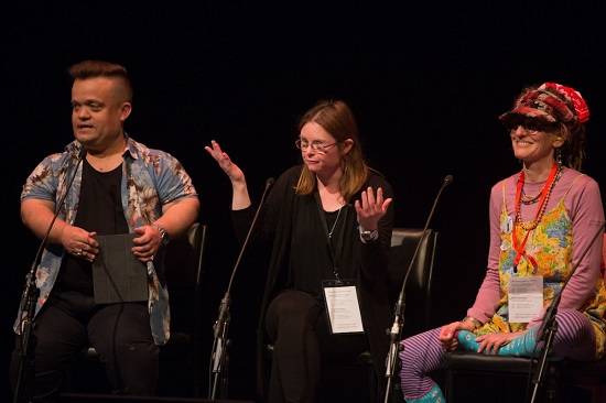 Image is of three people sitting on a panel at Meeting Place 2018. On right, is a person with short hair, wearing a black tshirt under a floral shirt and holding a tablet device. In the centre, a woman wears a black top and pants and wears glasses. To the left, a woman sits with one leg up on her chair. She smiles and wears a red hat and glasses and a red striped top and leggings under a floral dress.