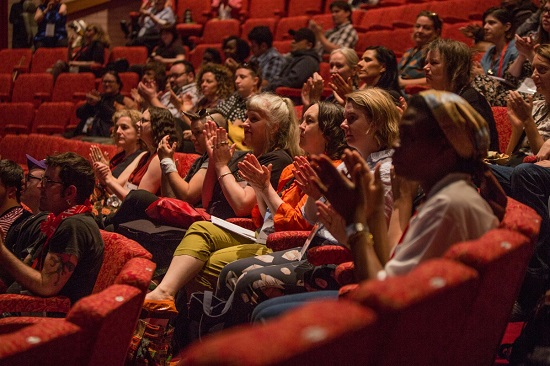 Image is of audience members at Meeting Place 2018. A group of people sit in red chairs in a theatre.