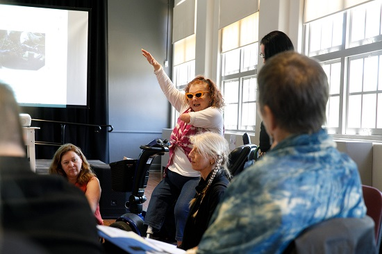 Artist Kath Duncan speaks to a group at Meeting Place 2019 from her spot sitting sideways on her mobility scooter, one arm raised in the air. She wears bright orange sunglasses, a tie-dyed top and a prosthetic leg. Part of a stage and projector screen image can be seen to her right.